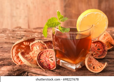 A glass of Bael fruit tea with lemon slices and mint leaf on a rustic wooden background. Beal beverage, Close up, Selective Focus.