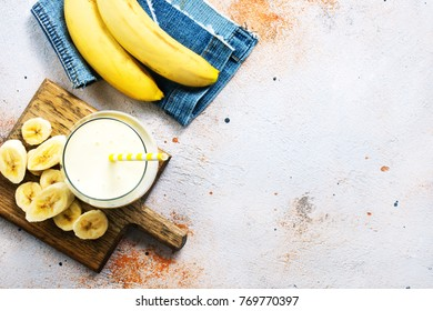 Glass of banana milk shake on the wooden table