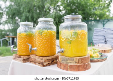 Glass bank of lemonade with sliced citrus fruits on a buffet table. Summer party outdoor. Detox.
