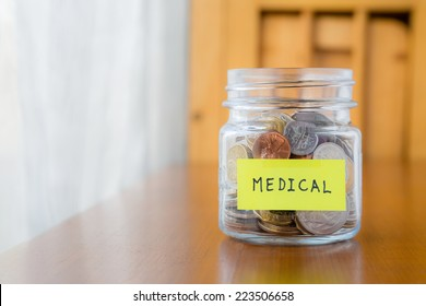 Glass bank with many world coins and  medical word or label on saving money jar