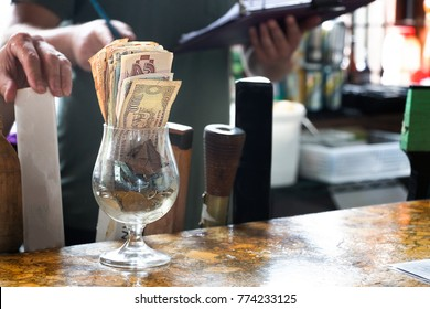 A glass with banknotes and coins for tips at a bar table, indoors.