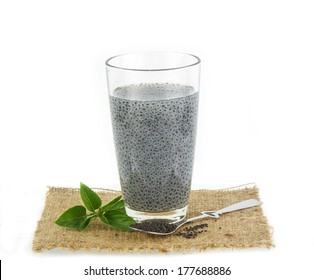 glass of basil seeds and raw seed against  white background