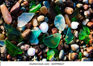 Glass beach. Natural texture with polished sea glass, stones and sand