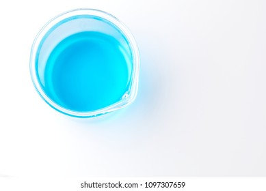 Glass beaker of copper sulfate solution (copper chloride) blue liquid isolated on white reflective background with shallow depth of field (top view). Science scientific concept