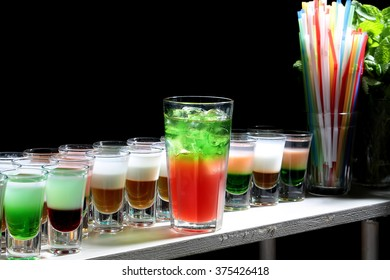 Glass of beautiful tasty sweet bright red green cocktail beverage with cold ice standing on bar near row of multicolored shots drinks and sipping straws closeup studio on black background, horizontal
