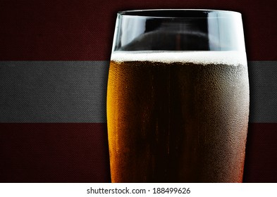 A glass of beer. Austria flag in the background. One of the countries where beer consumption is highest in the world.