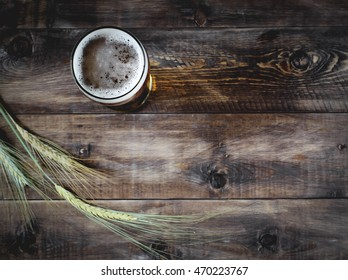 Glass of beer and barley on a wooden background