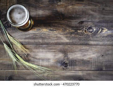 Glass of beer and barley on a wooden background.Top view