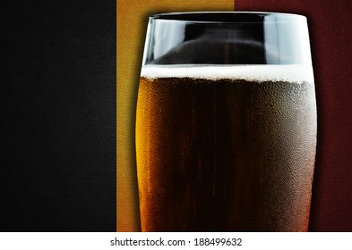 A glass of beer. Belgium flag in the background. One of the countries where beer consumption is highest in the world.