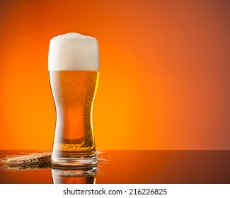 Glass of beer with blur orange background