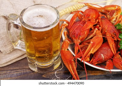 Glass of beer and a boiled crayfishes in a plate  on a wooden background, top view