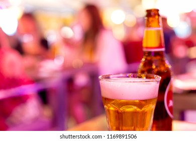 Glass of beer with bottle in extremely colorful crazy lighting
