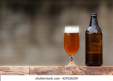 Glass of beer and bottle on wood table