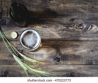 Glass of beer and bottle on a wooden background. Top view