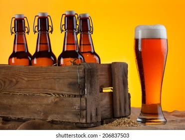Glass of beer with bottles in crate and barley still life