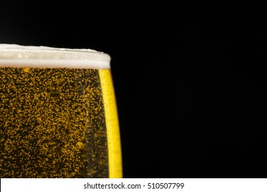 glass of beer with bubbles on black background with free space for text