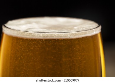 glass of beer with bubbles on black background closeup