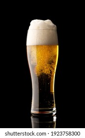 glass of beer with bubbles and thick white foam, isolated on black background