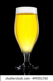 Glass of beer cider with foam golden color on black background