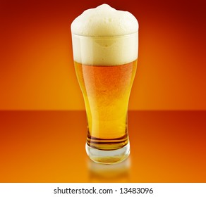 Glass of beer close-up with yellow background