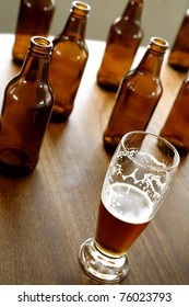 Glass of beer and empty bottles on table
