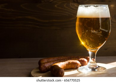 Glass of beer with foam and smoked sausages on  wooden background