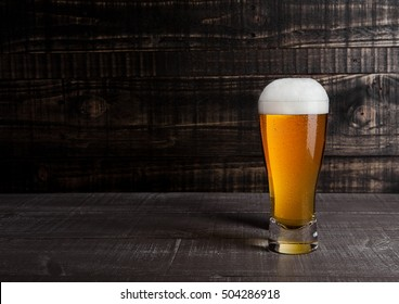 Glass of beer with frost frost on wooden background
