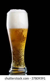 Glass of beer with froth over black background