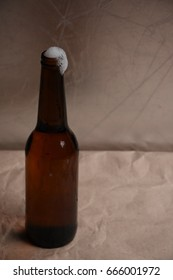 A glass of beer with a full bottle on the background