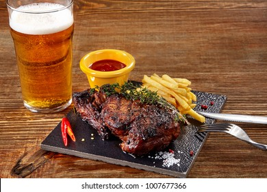 Glass of beer with gourmet steak and french fries on wooden background.