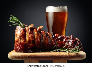 Glass of beer and grilled pork ribs with rosemary on a wooden board. Copy space.