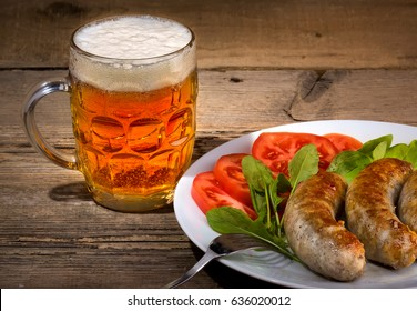 Glass of beer and grilled sausages on wood background