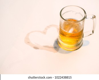 A glass of beer with a heart shape of water stain on the paper fit for valentine concept