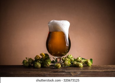 Glass of beer with hops on vintage wooden board