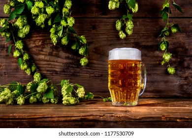 glass of beer and hops on wooden background
