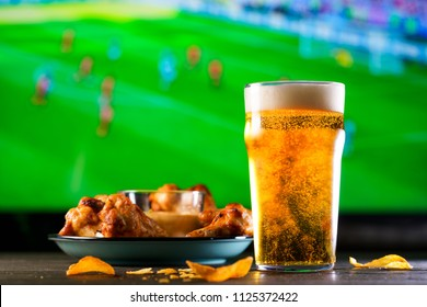 A glass of beer and hot chicken wings on a dark wooden table with crushed potato chips. Football on a background, high resolution