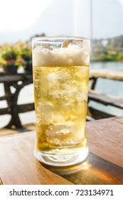 Glass of beer with ice on wooden table.