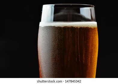 Glass of beer isolated on dark background