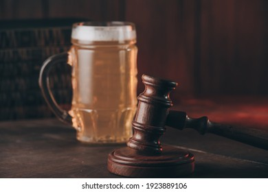 Glass of beer and judge gavel on a wooden table. Alcohol and crimes concept