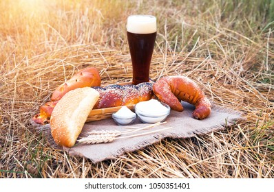 Glass of beer or kvass and breads with wheat ears on tablecloth, located on a dried hay. Fresh bread, bakery products and beer. Fresh beer