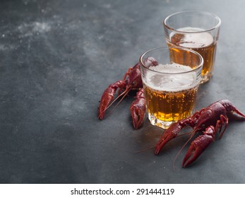Glass of beer and lobster on dark background, selective focus