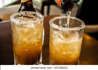 Glass of beer with mexican michelada mix and salt on the table.
