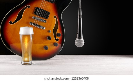 Glass of beer and microphone near electric jazz guitar on white wooden desk. Dark background.