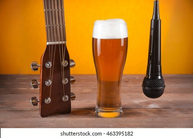 glass of beer and microphone near to guitar fretboard on wooden table