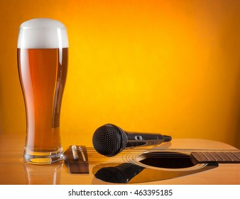 glass of beer and microphone standing on guitar. yellow background. empty space for text