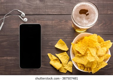 Glass of beer and nachos chips, smart phone, earphones on a wooden background.