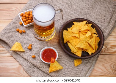 Glass of beer. Nachos chips. Tortilla snack. Mexican salsa nuts. Appetizer with sweet salsa or chilli sauce. Mug or pint of ale. On rustic sackcloth background.