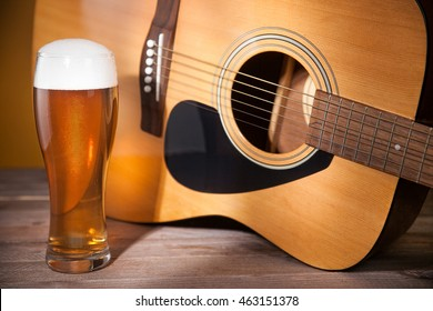 glass of beer near acoustic guitar.