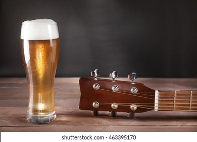 glass of beer next to guitar fretboard on wooden table