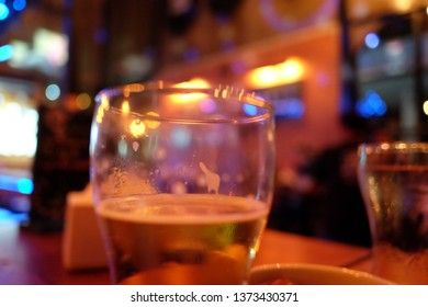 Glass of beer in night clue with night light bokeh. Party and hangout concept background.